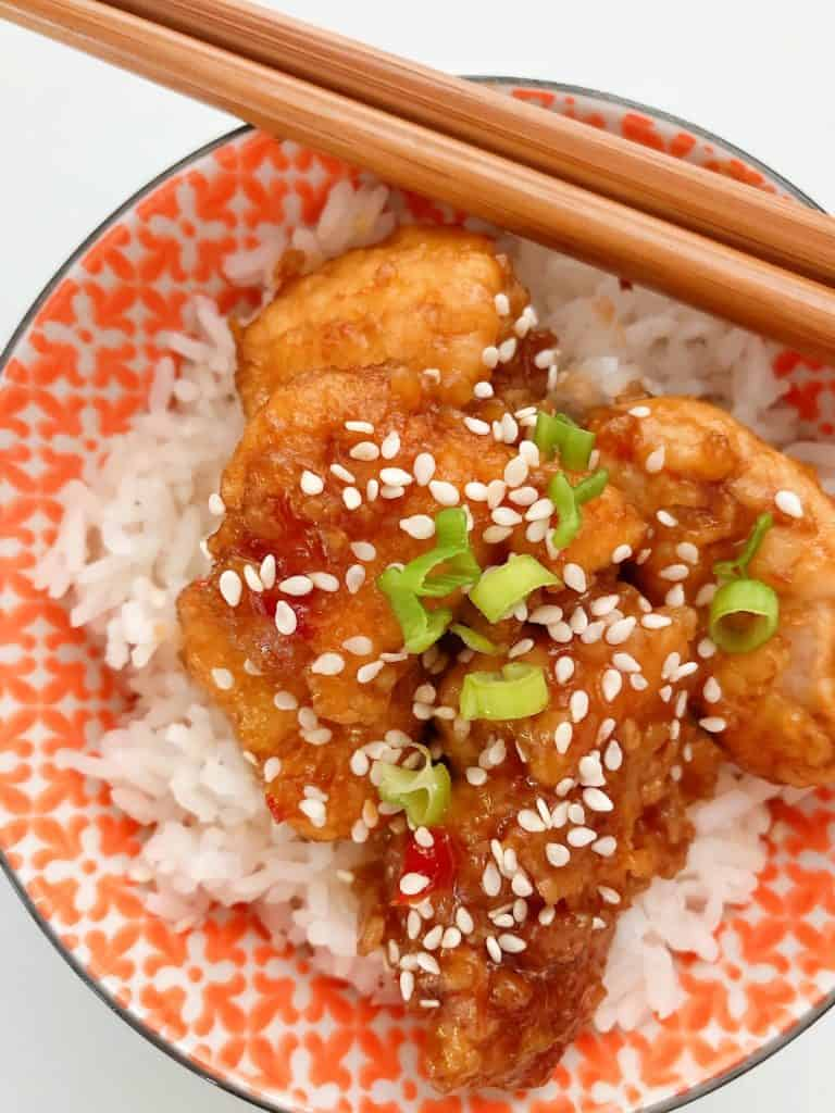 Sesame Chicken in bowl with chopsticks