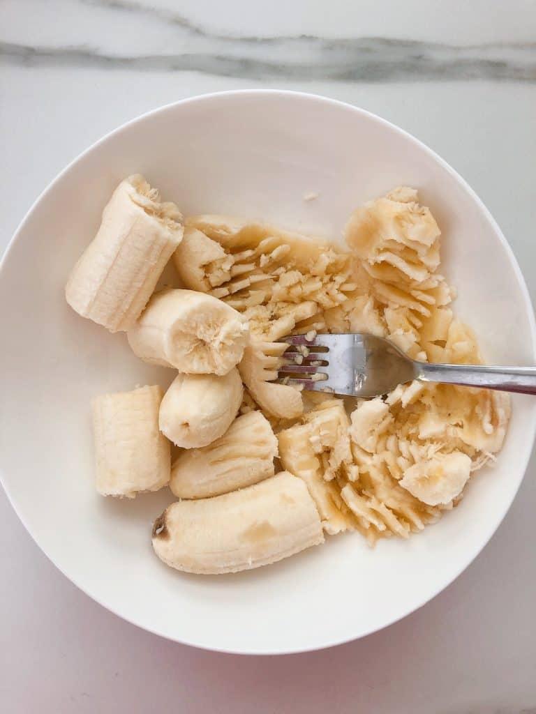 mashing banana with fork for choc chip banana muffins