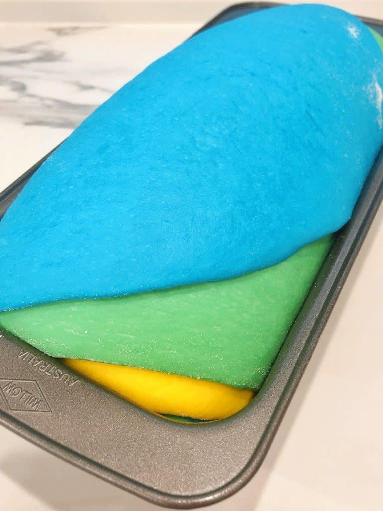 Rainbow bread dough proving in tin
