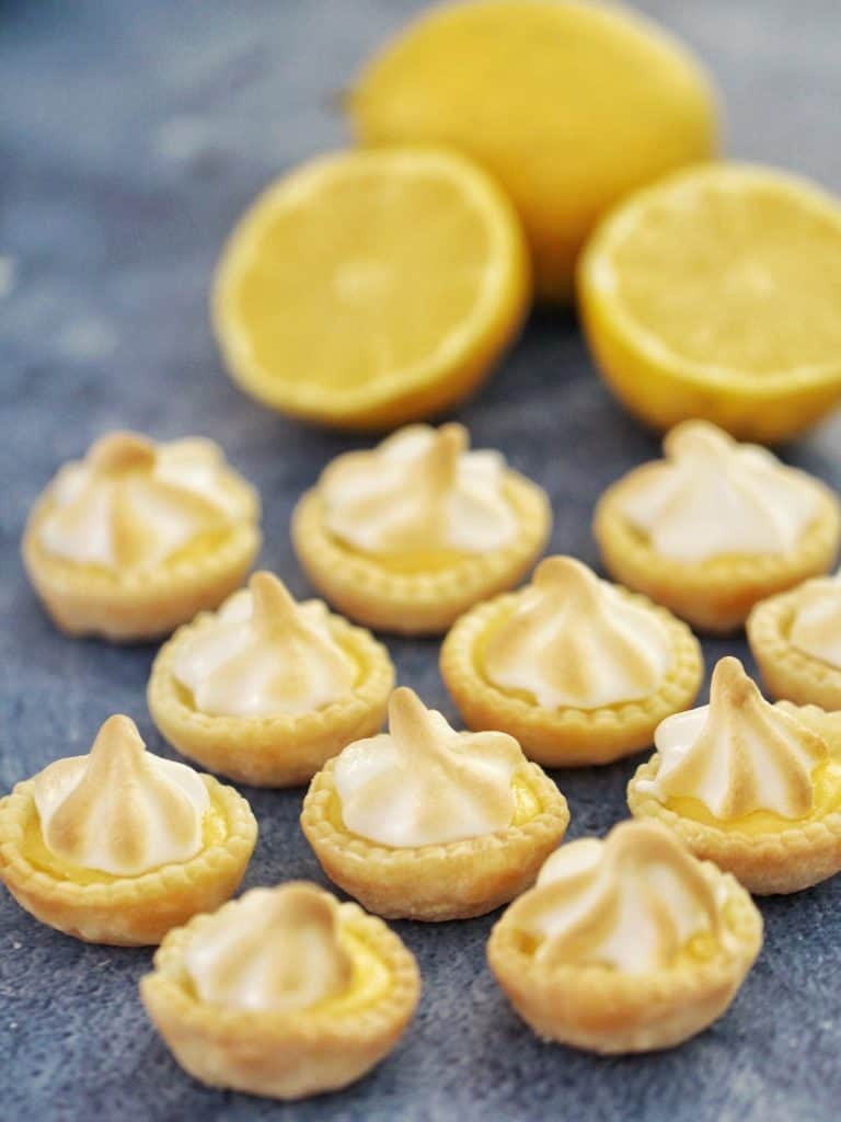 Mini lemon meringue tarts on table with lemons
