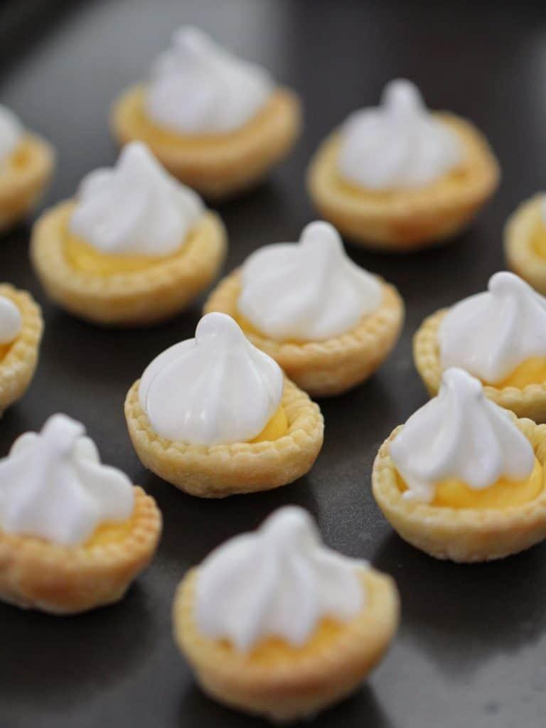 Meringue piped on top of lemon curd tarts