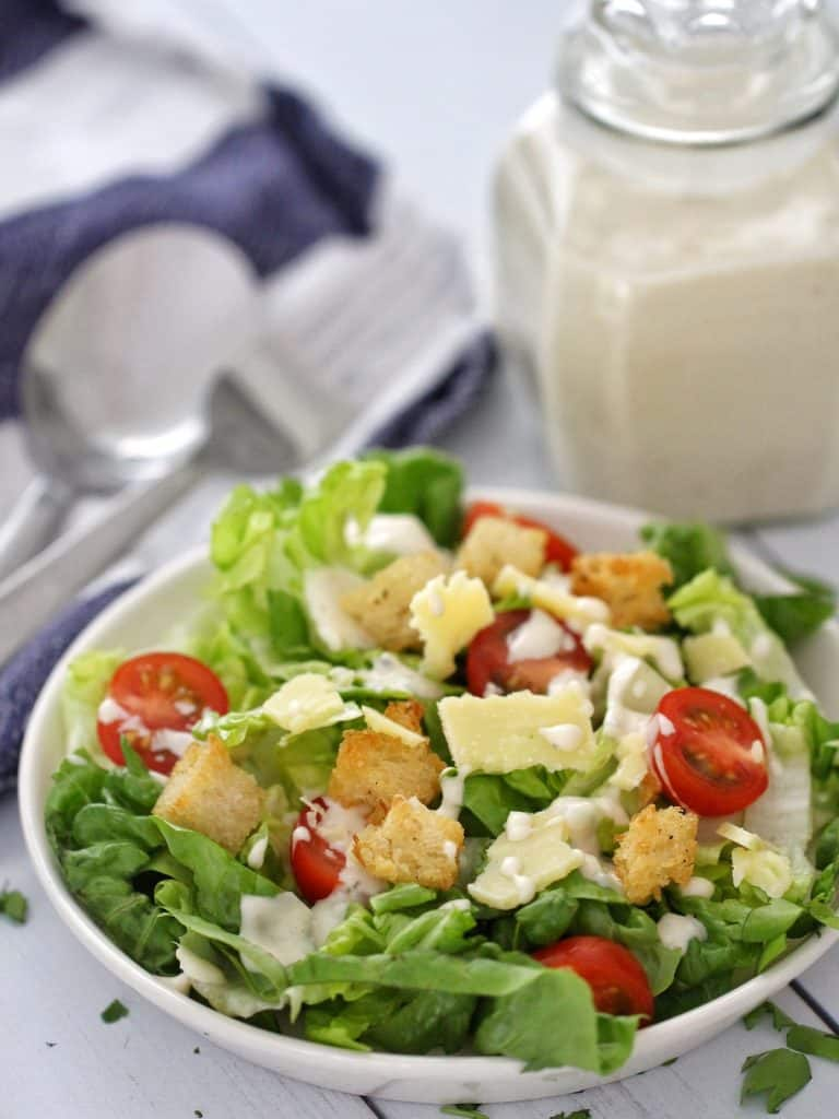 Caesar salad on plate with jar of Thermomix Caesar dressing