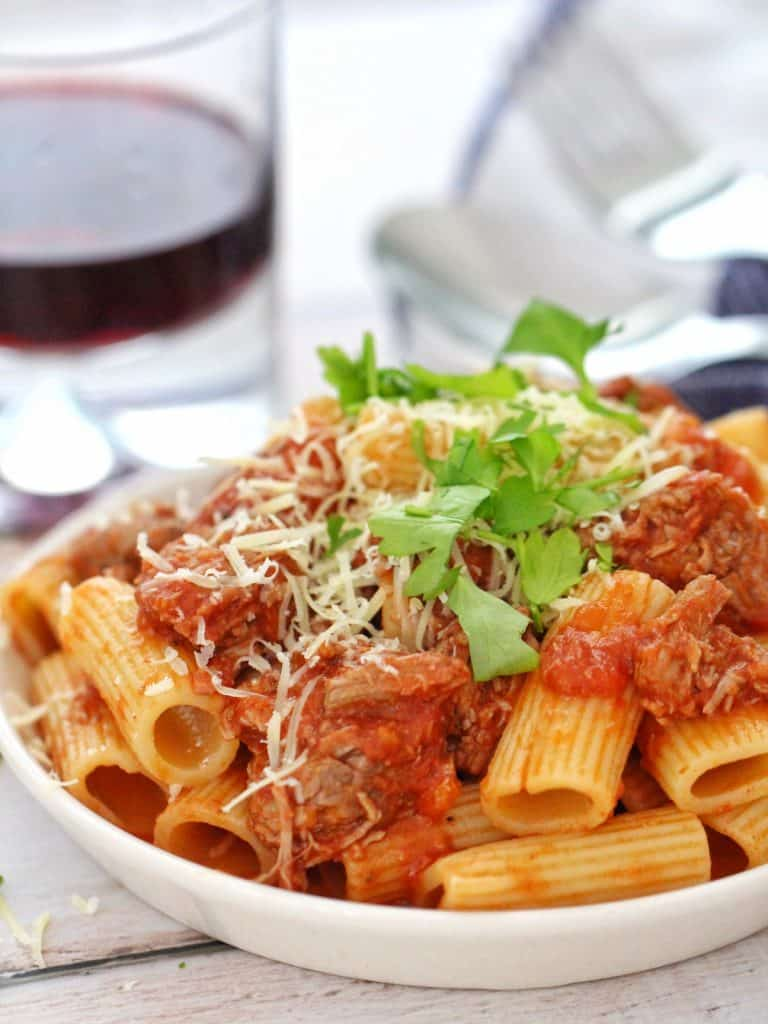 Slow cooked lamb ragu with rigatoni in a bowl with parmesan and parsley