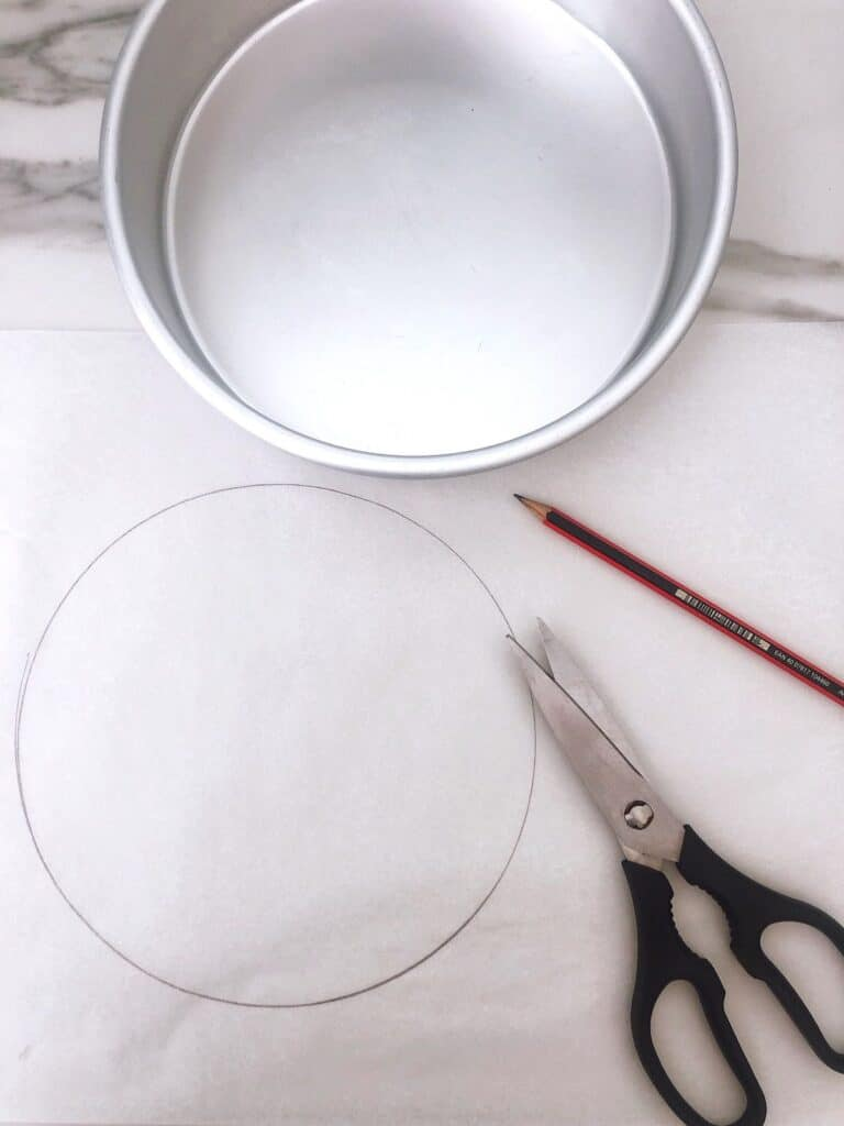 Cake tin sitting on parchment paper with scissors and pencil