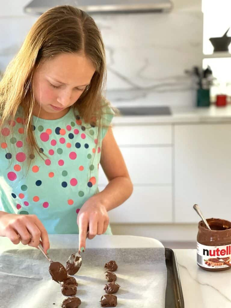 Scooping Nutella onto tray for Nutella stuffed Cookies