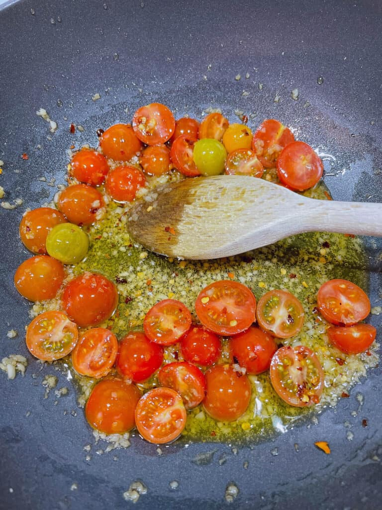 Cooking garlic and tomatoes for prawn aglio olio