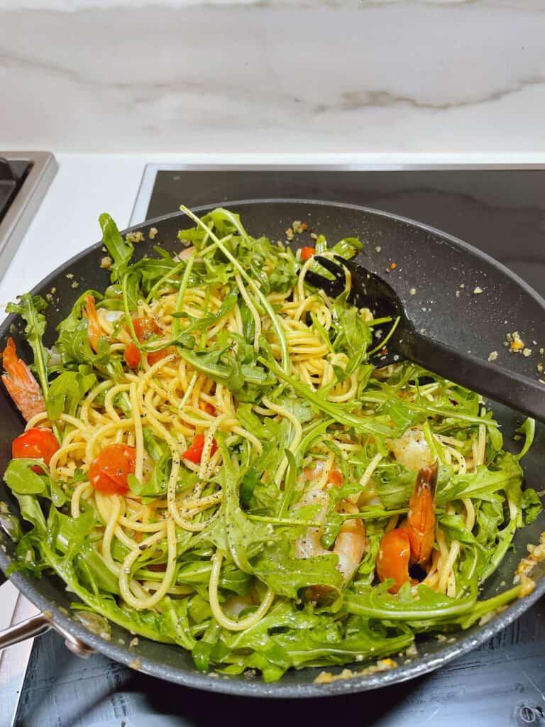 Mixing in rocket to prawn spaghetti